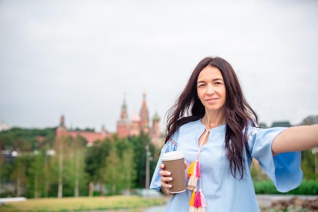 Caffè bevente della giovane donna urbana felice in città europea.