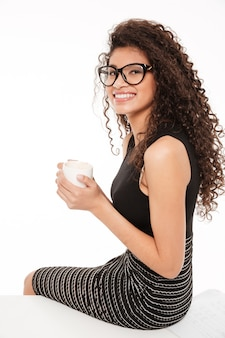 Caffè bevente della giovane signora africana riccia splendida.