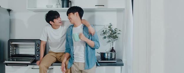 Caffè bevente delle coppie gay asiatiche, divertendosi a casa. i giovani uomini lgbtq + che parlano felici si rilassano insieme riposano insieme il tempo romantico nella cucina moderna a casa la mattina.