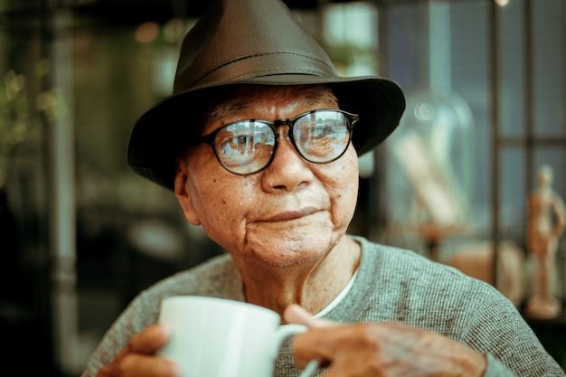 Caffè bevente di pensione asiatica del vecchioir di senoir nel sorriso del caffè e nel fronte felice