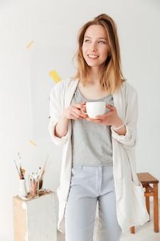 Caffè bevente felice giovane pittore caucasico della signora.