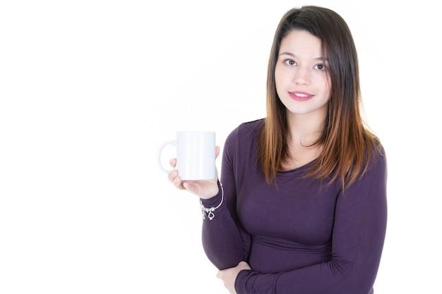 Caffè bevente o tè caucasico della giovane donna che sorride alla macchina fotografica con lo spazio bianco in bianco della copia