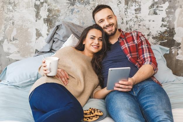 Caffè bevente o tè delle giovani coppie felici a letto alla mattina. leggere notizie, usare il tablet.