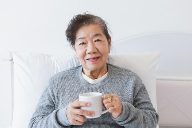 Caffè bevente o tè senior asiatico della donna anziana sul letto