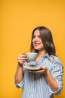 Caffè bevente sorridente della giovane donna alla moda in tazza grigia