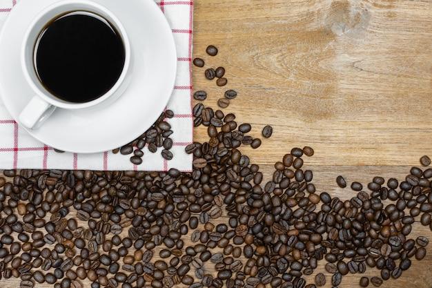 Caffè caldo con chicchi di caffè su fondo di legno