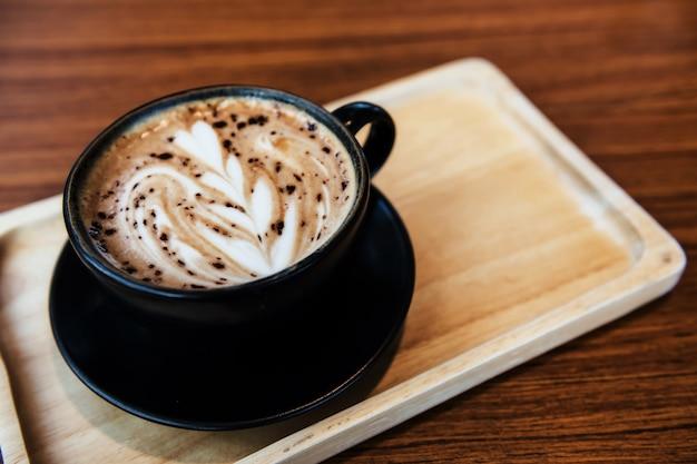 Caffè caldo con schiuma di arte floreale di latte