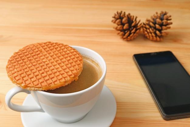 Caffè caldo con stroopwafel servito sul tavolo di legno con smart phone sfocato e pigne secche