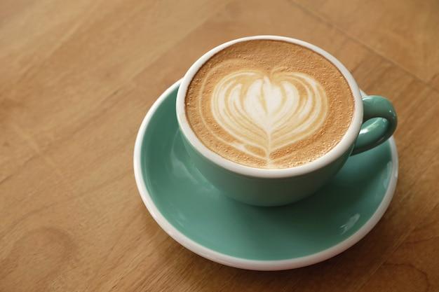 Caffè caldo del latte di arte sulla tavola di legno