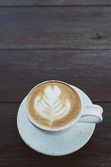 Caffè caldo in tazza bianca sul tavolo di legno