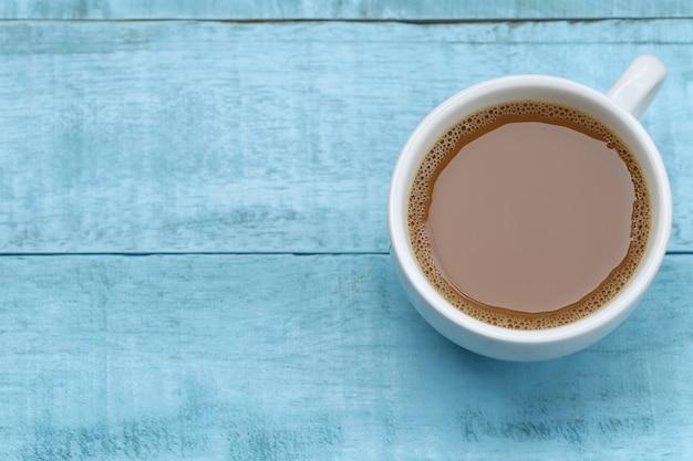 Caffè caldo in una tazza di caffè bianco sul tavolo di legno blu.