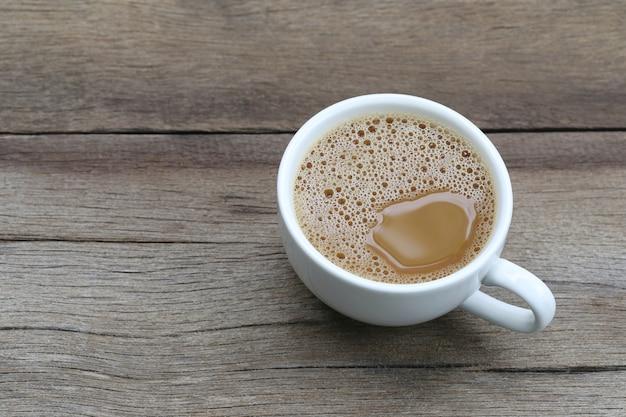 Caffè caldo in una tazza di caffè bianco sul tavolo di legno.