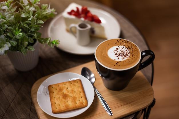 Caffè caldo in una tazza sulla tavola di legno