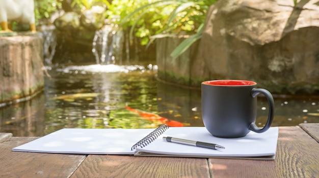 Caffè caldo, libro e penna posti vicino a un laghetto di carpe fantasia.