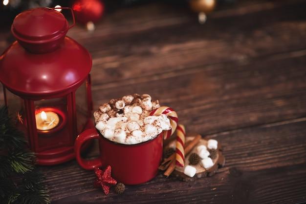 Caffè caldo panna montata invernale in una tazza rossa con biscotti a forma di stella e sciarpa calda -