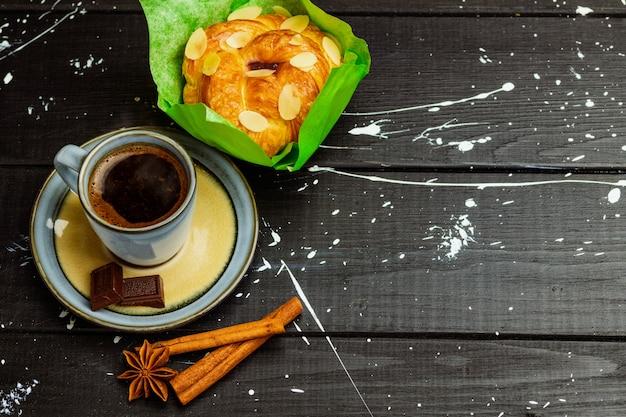 Caffè con cannella e dolce su una tavola di legno nera