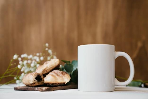 Caffè con croissant e fiori sfocati sullo sfondo