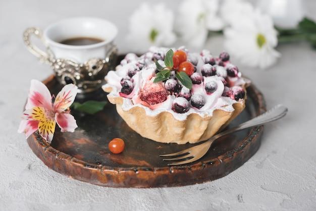 Caffè con crostata di frutta gustosa e fiori sul vassoio in legno