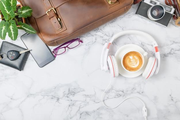 Caffè con cuffia e borsa in pelle vintage, smartphone e fotocamera vintage