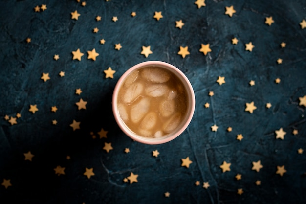 Caffè con ghiaccio e latte in un bicchiere su uno sfondo di pietra blu scuro con stelle. bevanda rinfrescante di concetto, sete, estate, cielo stellato, vita notturna, insonnia. vista piana, vista dall'alto