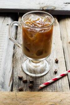 Caffè con ghiaccio in vetro e chicchi di caffè