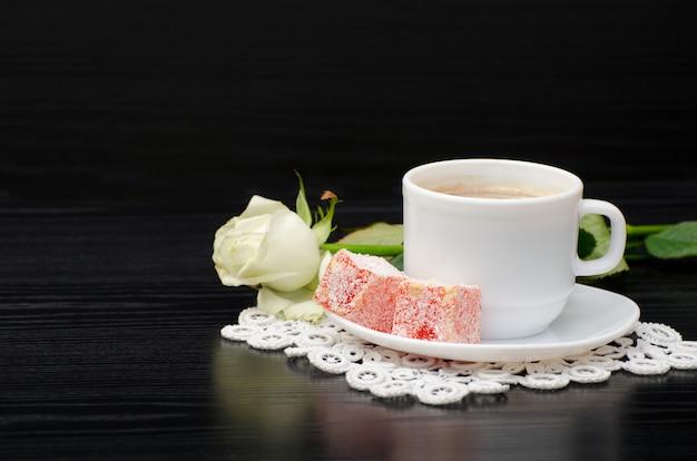 Caffè con latte, delizia turca, rosa bianca su un tavolo nero
