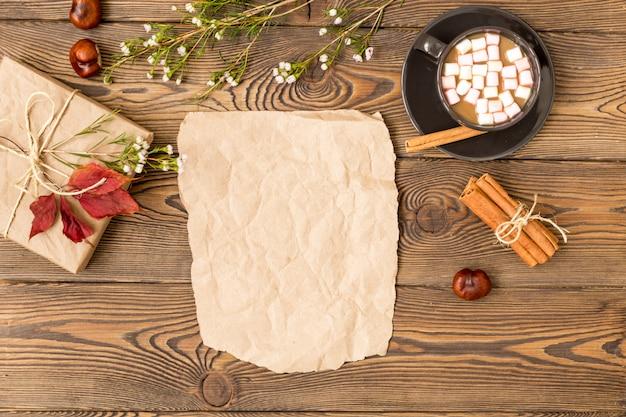 Caffè con latte e marshmallow, foglie di bastoncini di cannella e castagne su fondo di legno.