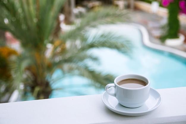 Caffè con latte in una tazza bianca sul balcone dell'hotel.