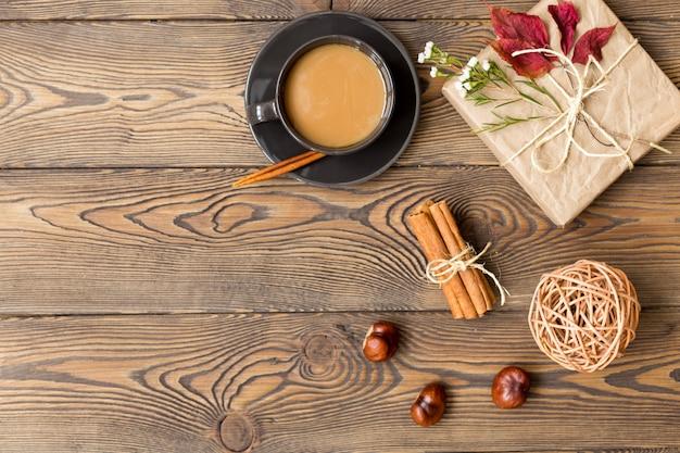 Caffè con latte, regalo, foglie di autunno, bastoncini di cannella e castagne su fondo di legno.
