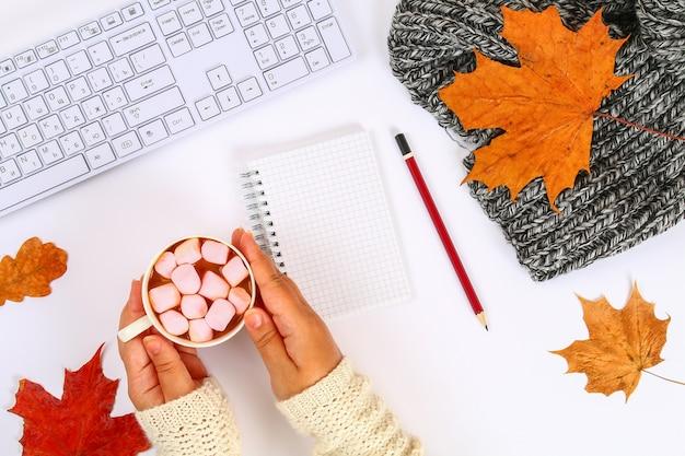 Caffè con marshmallow in mani sul desktop bianco accanto a un blocco vuoto e tastiera