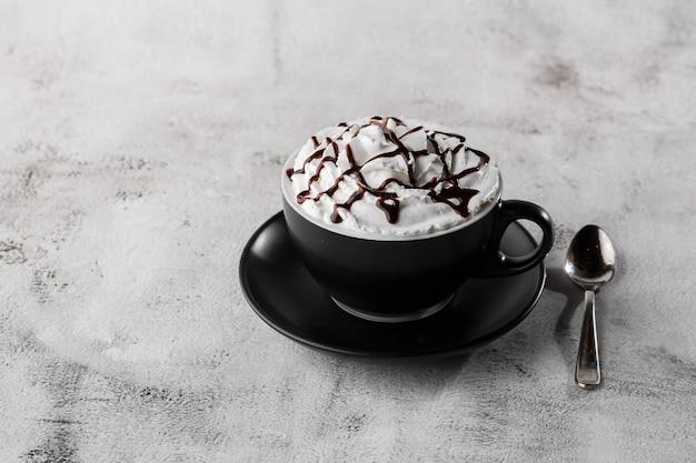 Caffè con panna montata e topping al cioccolato. caffè ghiacciato in tazza scura isolato su sfondo di marmo luminoso. vista dall'alto, copia spazio. pubblicità per menu bar. menu della caffetteria. foto orizzontale.