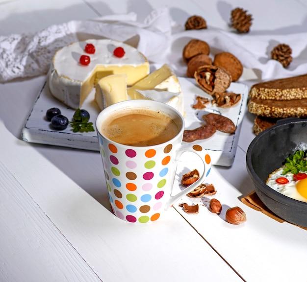Caffè con schiuma marrone in una tazza di ceramica bianca, dietro un formaggio rotondo al camembert