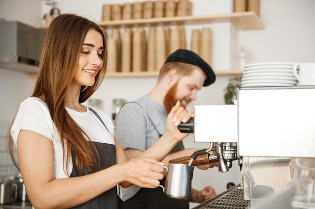 Caffè concetto di business - ritratto di signora barista in grembiule preparazione e vapore latte per l'ordine di caffè con il suo partner mentre in piedi al caffè.