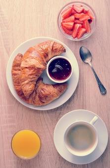 Caffè, cornetto con marmellata, fragole e succo d'arancia su fondo di legno