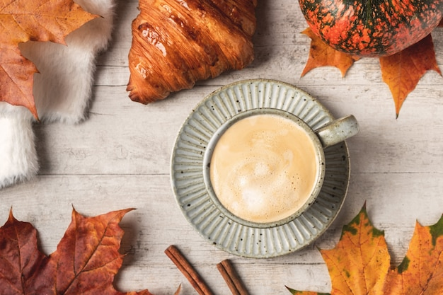 Caffè, cornetto, zucca, maglione bianco soffice su sfondo bianco e foglie di acero.