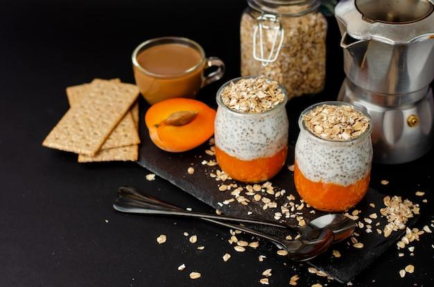 Caffè, cracker, budino di chia yogurt con albicocca fresca e fiocchi d'avena per la colazione sul nero