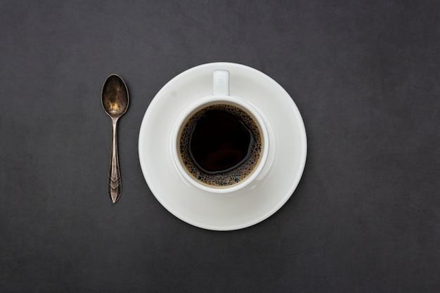 Caffè. cucchiaio e piatto bianchi di vista superiore della tazza di caffè su fondo scuro