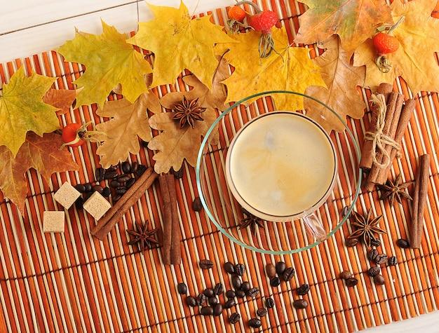 Caffè d'autunno con foglie gialle di quercia, acero e caffè in tazza di vetro trasparente, cannella e zucchero
