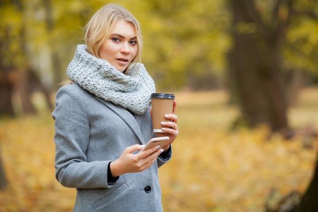 Caffè da portar via. giovane donna con caffè nel parco di autunno