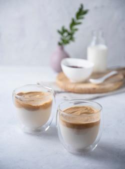 Caffè dalgona in bicchieri con latte vegano su sfondo chiaro