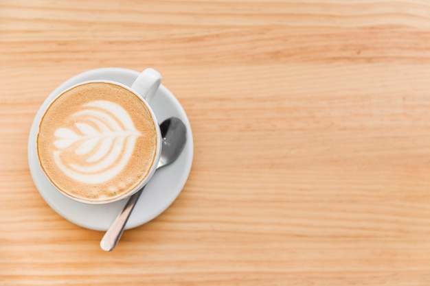 Caffè del cappuccino con arte latte e cucchiaio su fondo di legno