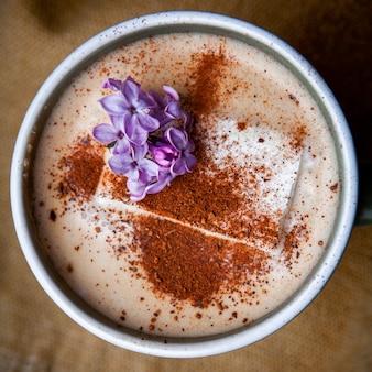 Caffè del cappuccino in una tazza con il primo piano dei petali del fiore sul pezzo di sacco