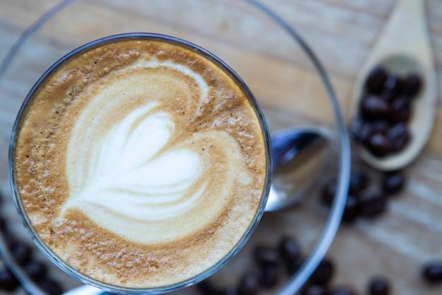 Caffè del latte del cuore, fagioli su una tavola di legno