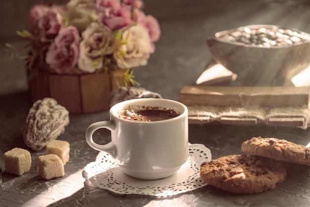Caffè del mattino con biscotti e pezzi di zucchero di canna al sole.