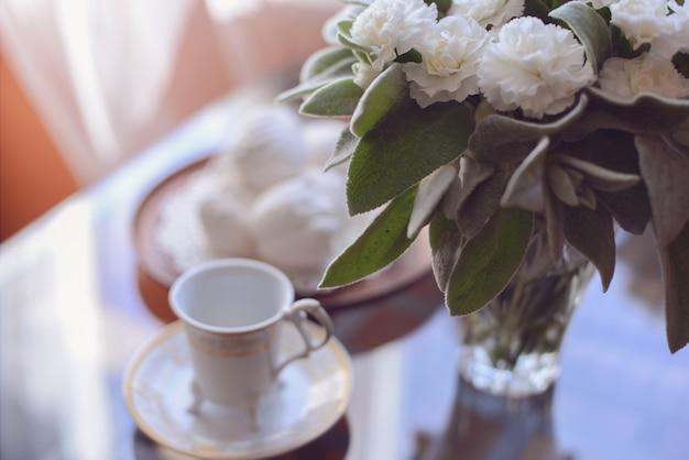 Caffè del mattino con un dessert bianco marshmallow arioso un mazzo di fiori freschi sul tavolo