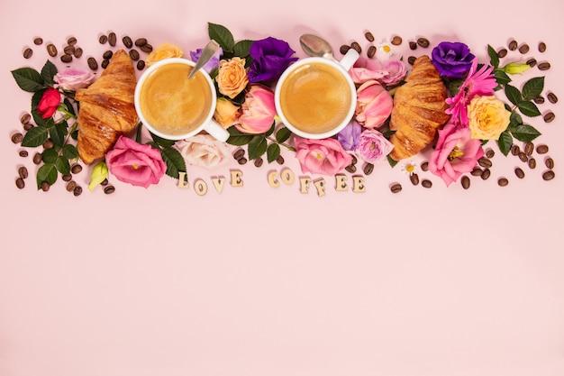 Caffè del mattino, cornetti e bellissimi fiori. stile piatto laico.