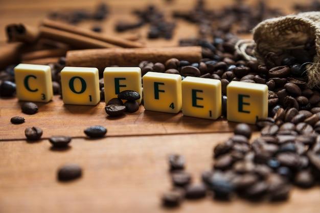 Caffè del primo piano che scrive vicino ai fagioli