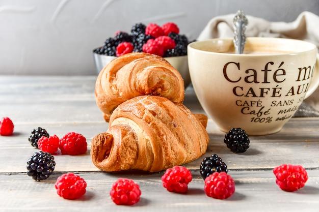 Caffè della colazione con latte e cornetti e lamponi e more freschi