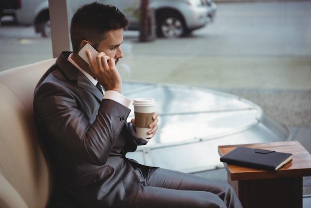 Caffè della tenuta dell'uomo d'affari mentre parlando sul telefono cellulare