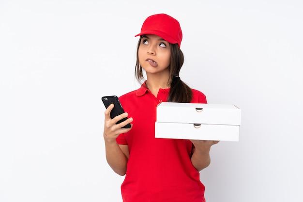 Caffè della tenuta della giovane donna di consegna della pizza da portare via e un cellulare mentre pensando qualcosa
